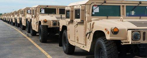 tan military trucks in a line run on machined parts by Ohio machine shop Lange Grinding and Machining